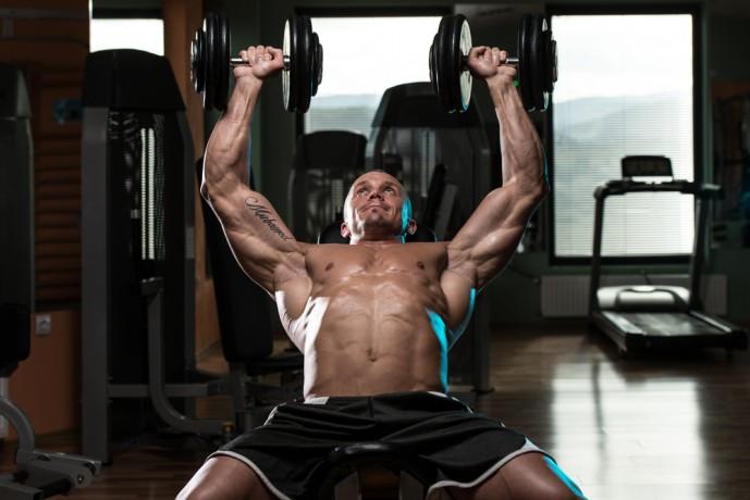 ダンベルショルダープレスで体を鍛える男