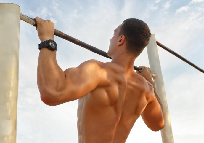 ワイドグリップチンニングで背筋に刺激を与える男性
