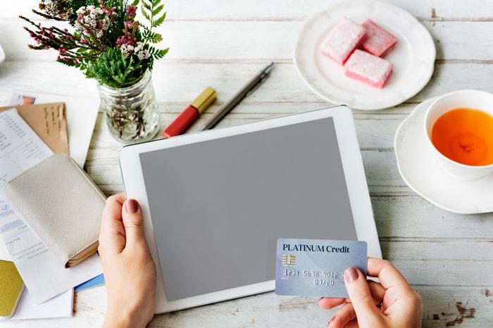 タブレット端末を見ながらクレジットカードを持つイメージつ