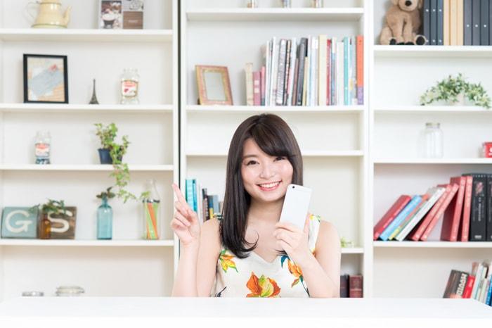 スマホをもって指を立てている女性のイメージ