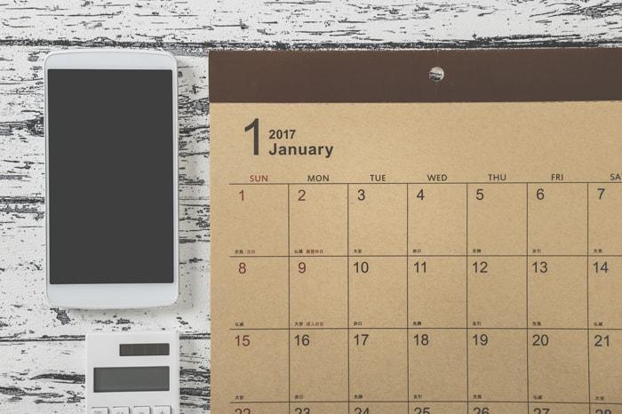 スマホと電卓とカレンダーが置いてあるイメージ