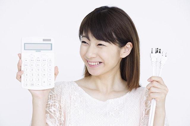 コンセントと電卓を持つ女性