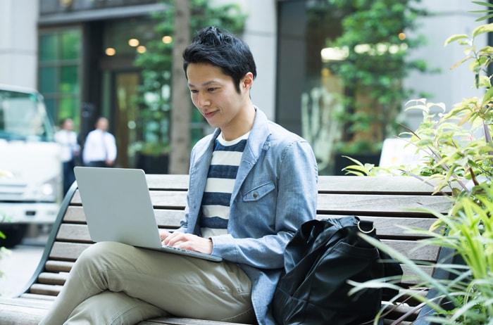 ベンチに座ってノートパソコンを見る男性
