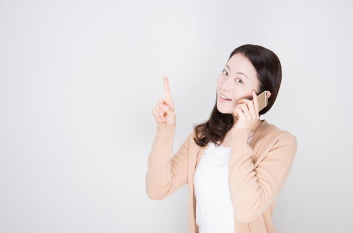 指を立ててスマホで電話する女性