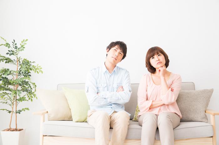 ソファーに座って考える男女