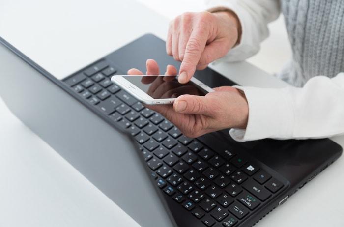 ノートパソコンを開きながらスマホを触る人