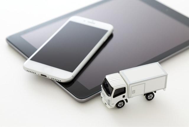 トラックの模型とスマホとタブレット