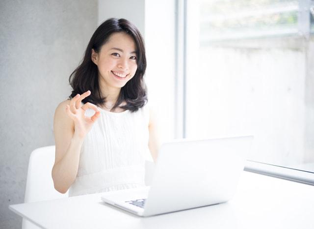 パソコンをしながらOKサインをする女性