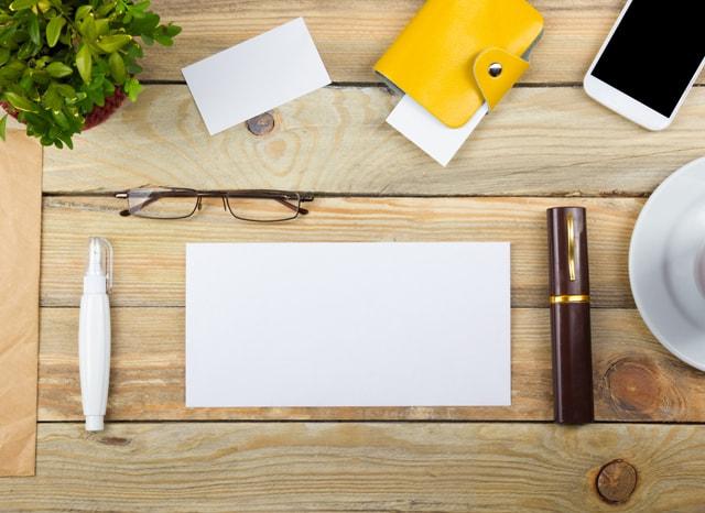 机にある筆記用具とスマホ
