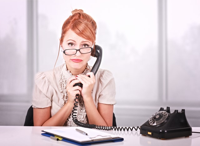 困った顔で黒電話に出る女性