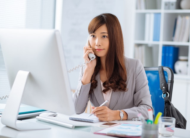 モニターを見ながら電話する女性