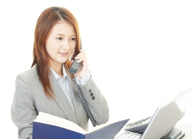 資料を見ながら電話をする女性