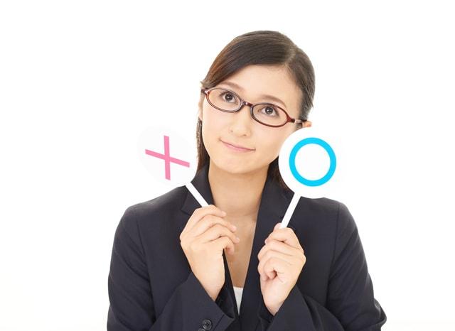 ○と×の札を持って考える女性