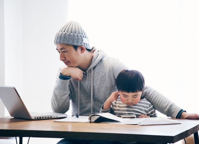 パソコンと本を見ながら困る親子