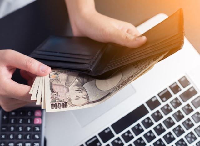 パソコンや電卓を見ながら財布からお金を出す人
