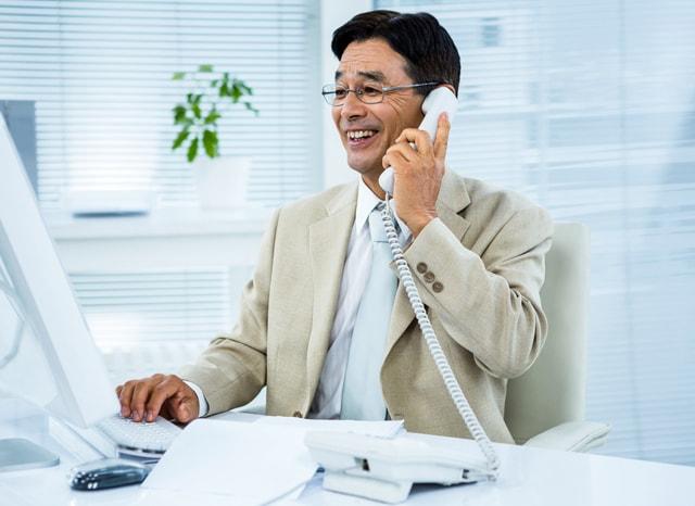 電話をしながら仕事をする実業家の男性
