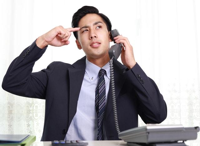 頭に指をつけながら電話する男性