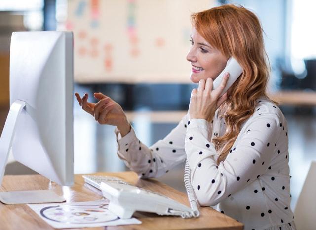 パソコンを見ながら電話をする女性