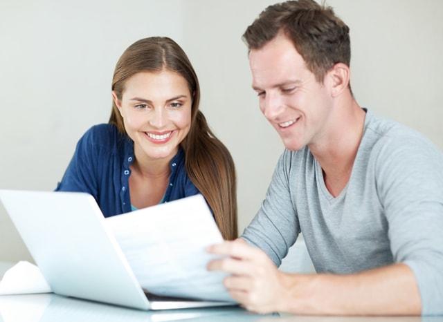 笑顔で書類を見る男女