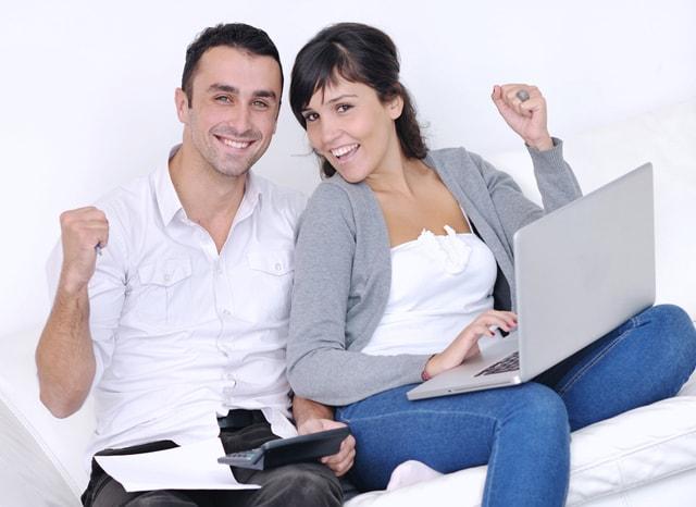 パソコンを開いてガッツポーズする夫婦