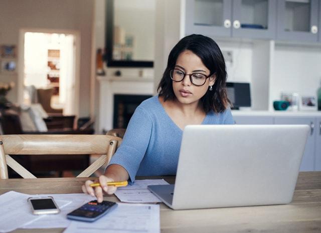 パソコンを見ながら電卓をたたく女性