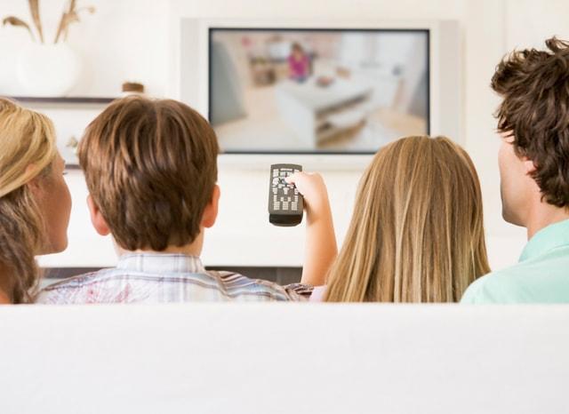 ソファーに座ってテレビを見る家族