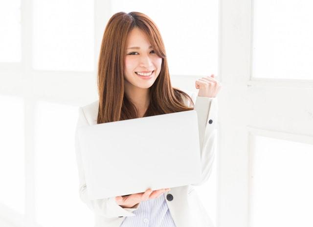 パソコンを持ってガッツポーズする女性