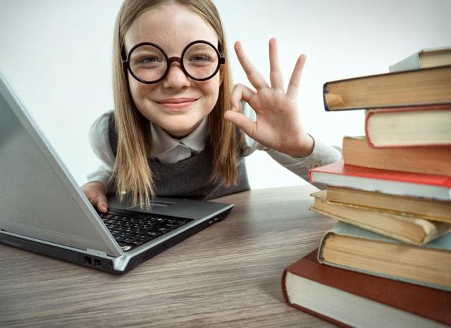 パソコンをしながらOKサインする女の子