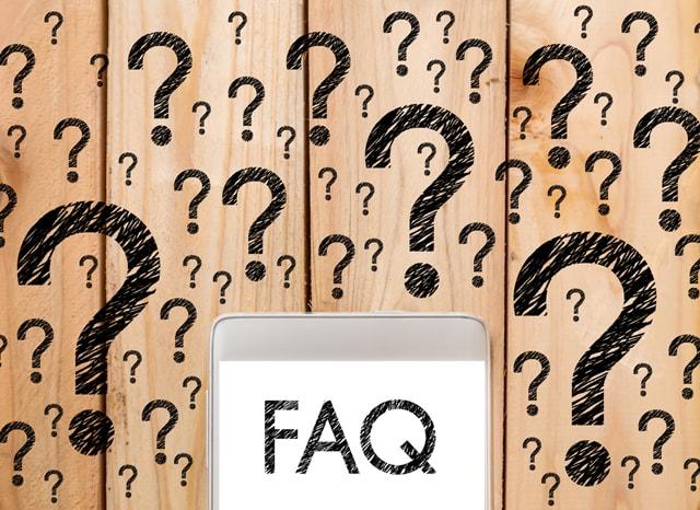 FAQ表示されたスマホと沢山のクエスチョンマークが書かれた壁