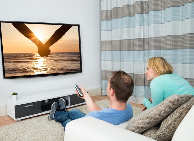座ってテレビを見る夫婦