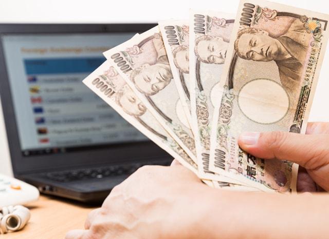 パソコンを開きながらお金を持つ人