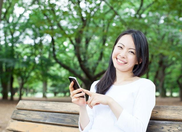 ベンチに座ってスマホを触る笑顔の女性