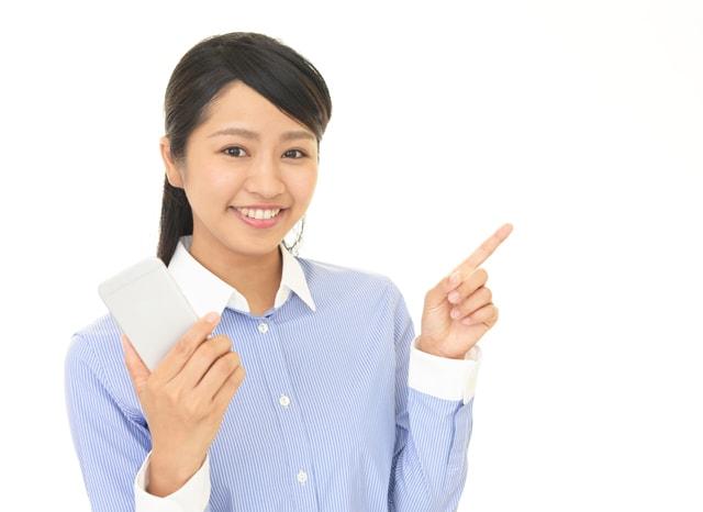 スマホを持ちながら指を向ける女性