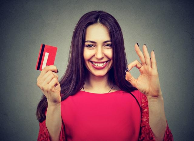 赤いカードを見せてOKサインする女性