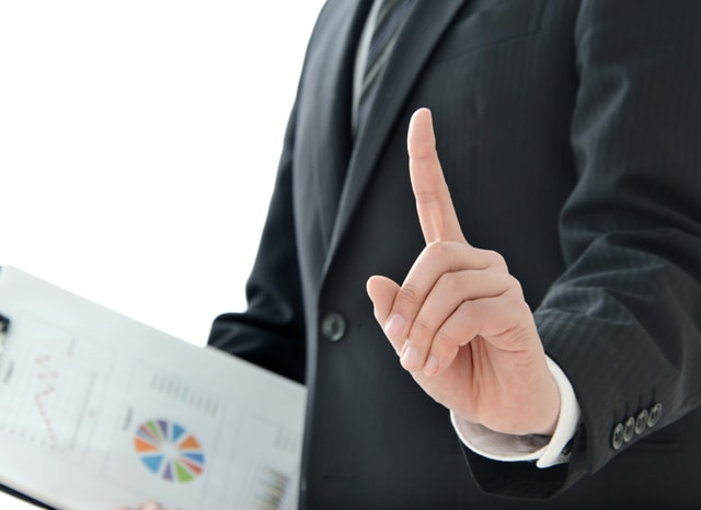 書類を片手に指を上げている人