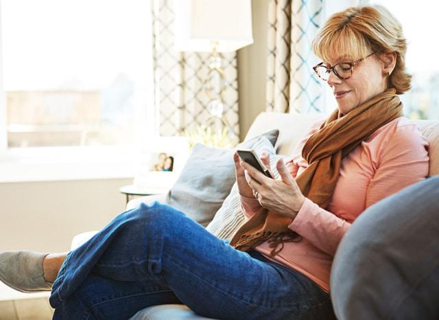 ソファに座ってスマホを見る女性