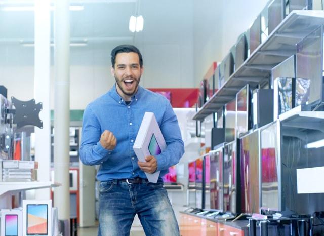 電気店でタブレットを買ってガッツポーズする男性