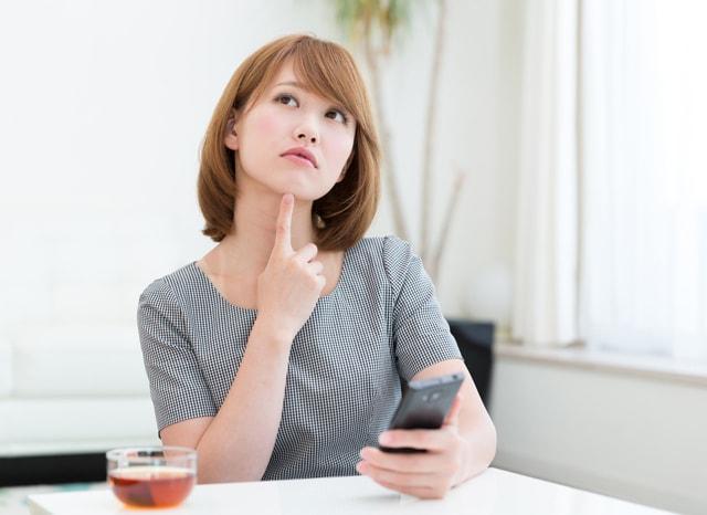 スマホをしながら考える女性