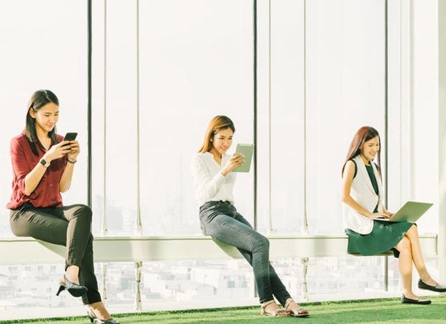 オフィスで座ってメディア機器を使用する女性達