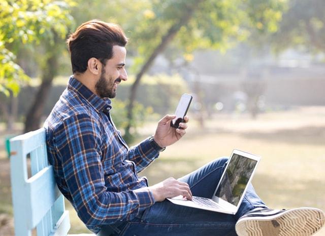 外でスマホを見ながらパソコンをする男性