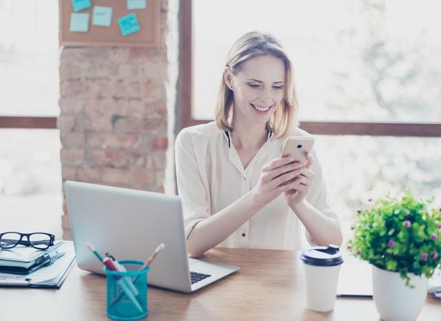 スマホを見ながらパソコンをする女性