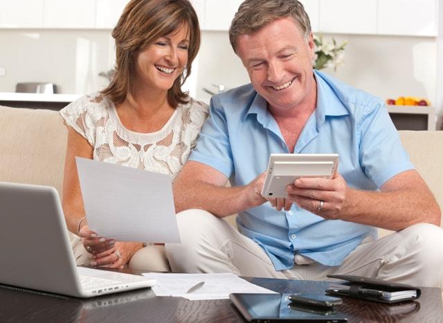 笑顔で電卓を見る熟年夫婦