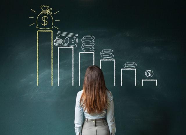 お金に関するグラフが書かれた黒板を見る女性