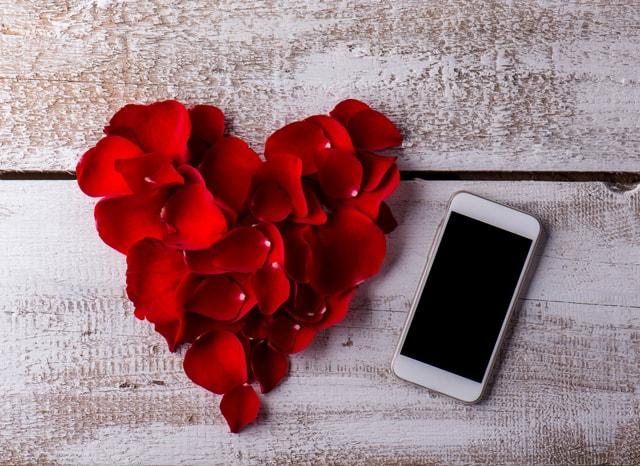 スマホとハートの形になっているバラの花びら
