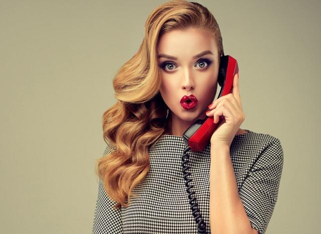 赤色の受話器で話す女性