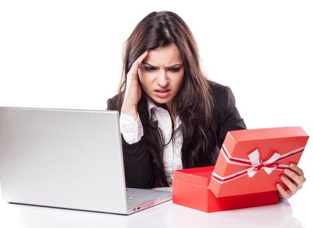 パソコンと空いたプレゼントを見て困惑する女性