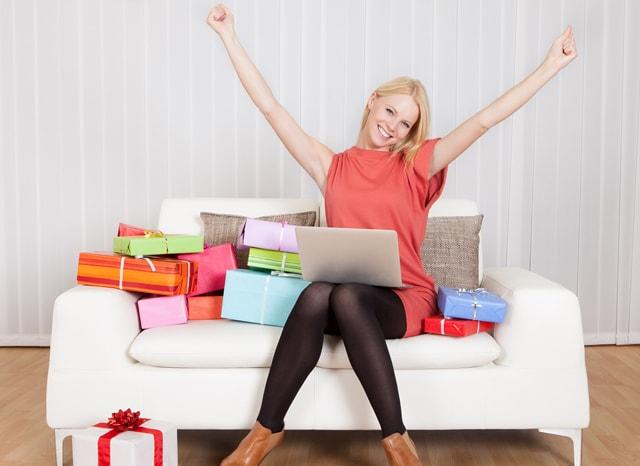 沢山のプレゼントが置かれたソファーでパソコンを開きながら両手を挙げて喜ぶ女性