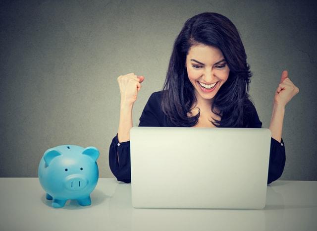 青い貯金箱とパソコンを見ながらガッツポーズする女性