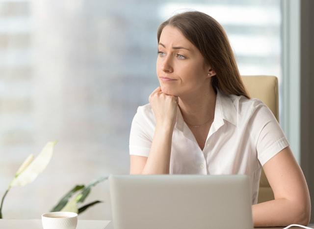 パソコンをしながら悩む女性