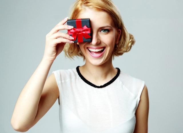 プレゼントで目を隠しながら笑う女性